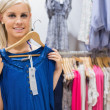 Woman holding up blue shirt and smiling - ストック写真
