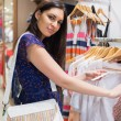 Woman with bag looking through clothes and smiling - Foto Stock