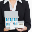Real estate agent holding a model house — Stock Photo