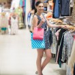 Woman standing at the clothes rack holding two bags - ストック写真