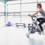 Woman riding an exercise bike — Stock Photo