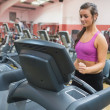 Woman running on a treadmill in a gym looking down — Stock Photo