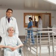Doctor pushing woman in a wheelchair — Stockfoto