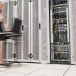Woman pushing computer through data center - Stock Photo