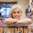 Woman leaning at a clothes rack smiling — Stock Photo