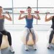 Three smiling women sitting on exercise balls and lifting weight — Stock Photo