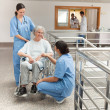 Two nurses talking with  old women sitting in wheelchair — Stock Photo