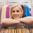 Woman leaning on clothes rack smiling — Stock Photo