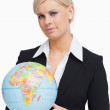 Serious businesswoman holding a globe — Stock Photo
