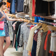 Woman searching through clothes holding two bags - ストック写真