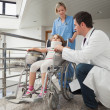 Stock Photo: Doctor crouching next to child in wheelchair with nurse pushing