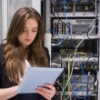 Stock Photo: Womusing tablet pc in front of servers