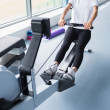 Energetic woman training on row machine — Stock Photo