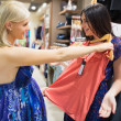 Woman holding shirt up to friend — Stock Photo #23048906