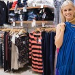 Woman holding up blue shirt in boutique - 图库照片