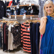 Woman holding up blue shirt in boutique - Stock fotografie