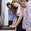 Stock Photo: Three technicians looking at laptop