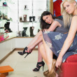 Women trying on shoes in shoe store — Stok fotoğraf