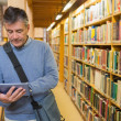 Man holding a tablet pc in a library — Stock Photo