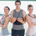 Trainer standing between two women — Stock Photo #23049364