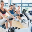 Stock Photo: Smiling woman on rowing machine with others
