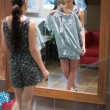 Woman is standing in front of the mirror with clothes - Stock fotografie