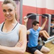 Stock Photo: Smiling female trainer with arms crossed