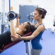 Concentrated trainer teaching woman lifting weights - Stock fotografie