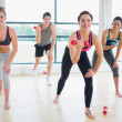 Smiling lifting wights in aerobics class — Stock Photo #23049552