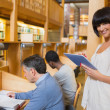Smiling woman holding a tablet pc in the library — Foto de Stock