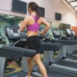 Woman running on a treadmill in a gym — Stock Photo #23049672