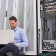 Man working with his laptop on the floor beside servers - Foto Stock