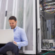 Man working with his laptop on the floor beside servers — Stock Photo #23049704