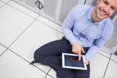Technician happily using tablet pc in data center — Stock Photo