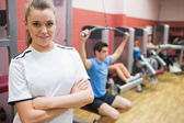 Woman with arms crossed standing in a fitness studio — Stock Photo