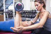 Woman lifting weights with trainer — Stock Photo