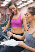Female trainer showing client her time on treadmill — Stock Photo