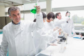 Chemist raising beaker of green liquid — Stock Photo
