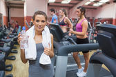 Happy woman drinking water in gym — Stock Photo