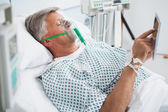 Patient is lying in bed reading in hospital ward — Stock Photo