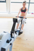 Woman sitting at the row machine pulling and smiling — Stock Photo