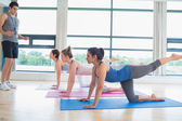 Male instructor with yoga class — Stock Photo