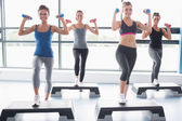 Four women lifting weights while doing aerobics — Stock Photo