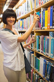 Black-haired woman taking a book out of the shelves — Stock Photo