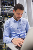 Man working on laptop in front of servers — Stock Photo