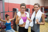 Two women with towels with woman using weight machine — Stock Photo