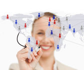 Woman linking figures on world map — Stock Photo