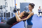 Woman lifting weights and her trainer — Stok fotoğraf