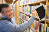 Smiling man taking a tablet pc from shelves — Stock Photo
