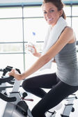 Woman riding an exercise bike and drinking water — Stock Photo